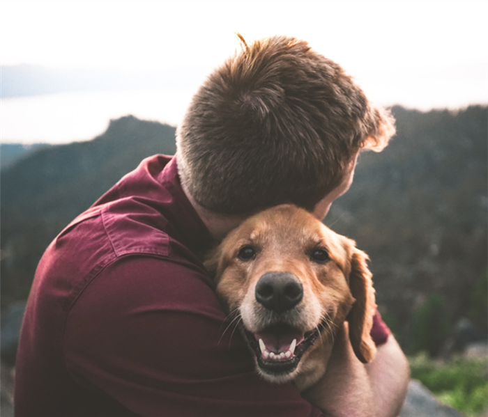 Male hugging a dog
