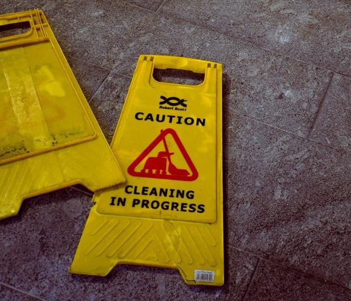 Yellow caution sign warning of floor cleaning in process